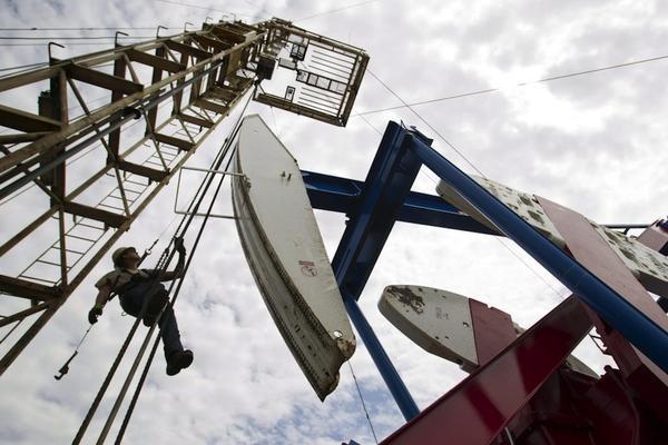 An-oil-field-worker-hangs-from-an-oil-derrick-outside-of-Williston-N.D..jpg