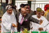 Business-mogul-and-Africas-richest-man-Alhaji-Aliko-Dangote-points-while-Godwin-Obaseki-waves-to-a-mutual-friend-at-his-inauguration-ceremony.-174x116.jpeg