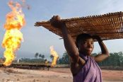 A-community-dweller-next-to-gas-flare-stacks-in-the-Niger-Delta.-e1532774304340-174x116.jpg